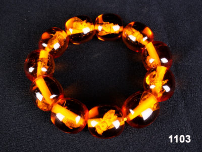 Modern amber colour elasticated bead bracelet with an insect in each bead from Antiques of Kingston