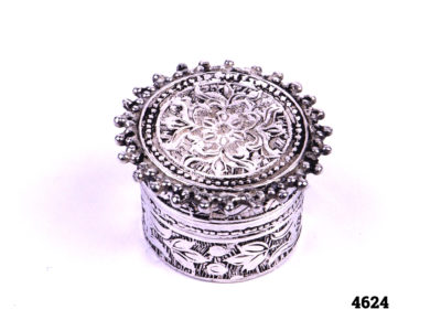 950 Sterling silver hallmarked small ornately decorated pill box with a flora design throughout Otherwise known as Britannia silver, 950 silver contains 95% silver to 5% alloy) Measures 25mm in diameter at base and 30mm across the top