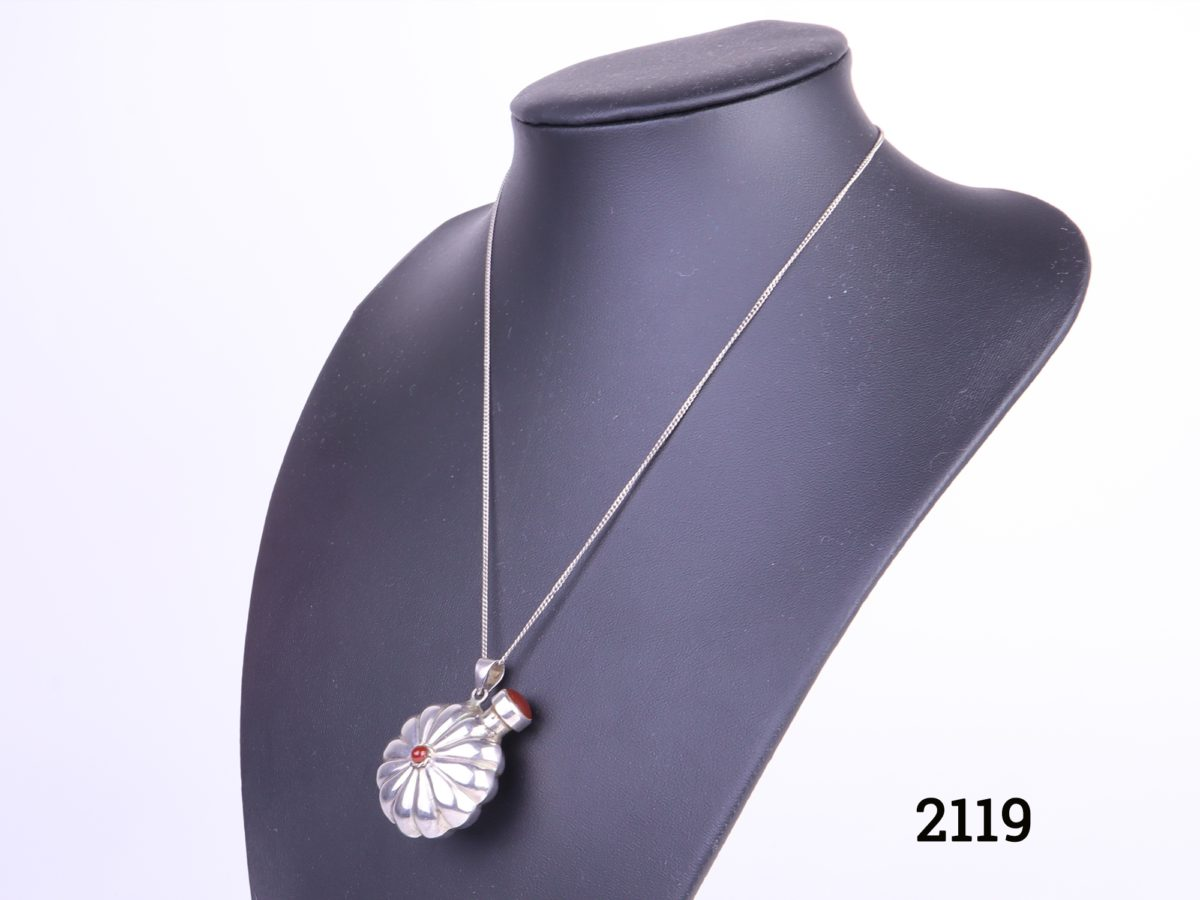 Silver scent bottle pendant on chain with carnelian stone accent Side angle photo showing necklace and pendant on display stand