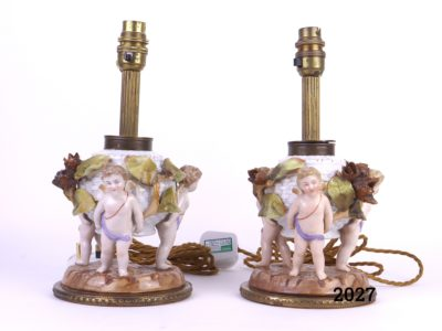 Antique pair of Continental porcelain lamps decorated with 3 winged cherubs holding a basket with leaves & beech nut seed pods Measures 140mm in diameter at base Main photo showing the pair of lamps