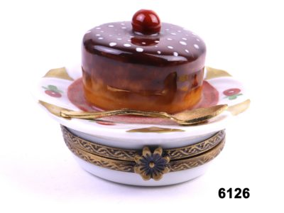 Small Limoges hand-painted porcelain box in the form of a dessert pudding on a plate with a gilt spoon Main photo front view