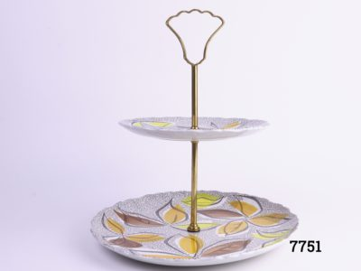 1960s two tier cake stand with gilt metal handle and rod Made at the Old Foley potteries by James Kent ltd England Acid & detergent proof colours Bottom plate measure 225mm in diameter & top measures 160mm in diameter Main photo showing whole cake stand from side on view