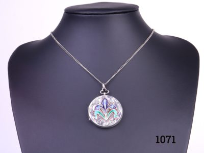 Enamelled locket on chain Art Nouveau style sterling silver locket with enamelled iris flower to the front on a white metal chain Pendant measures 33mm in diameter and weighs 13.1g Main photo of whole necklace on display stand