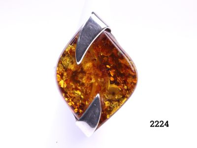 Front view of Modernist style amber ring with large synthetic amber set on sterling silver. Hallmarked 925 with makers initials SG. Size O / 7.25.