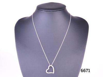 Silver heart pendant encrusted with cubic zirconia pieces on 925 sterling silver chain Pendant measures 22mm by 20mm and hangs slightly to the side Main photo showing necklace displayed on stand
