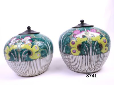 Pair of 19th century Canton vases/preserve pots with wooden lids (Some slight size difference) Larger pot has same design on front & back smaller one has different designs Measures 145mm in diameter at base and 230mm at widest point Main photo showing both vases side by side