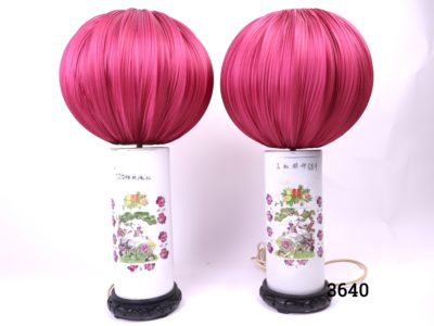 Pair of Chinese wig/hat stands on wooden stand up-cycled into lamp bases with Chinese lantern shaped cerise silk shades Base measures 130mm in diameter at base and 330mm tall Shades are 320mm in diameter and 245mm high Main photo of the 2 lamps