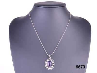 925 Sterling silver and amethyst cabochon pendant on a sterling silver snake chain Pendant drop length 32mm Measures 24mm by 18mm Chain measures 405mm long Weight 9.4g Main photo of necklace displayed on a stand