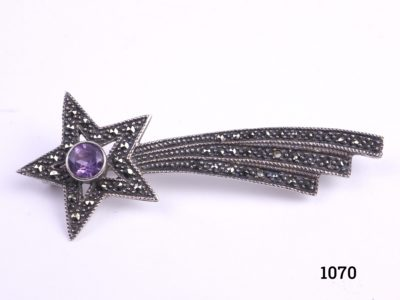 Silver shooting star brooch set with marcasite and small amethyst stone to the centre of the star Hallmarked 925 for sterling silver Main photo of the front of brooch