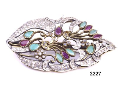 c1940s Sterling silver brooch with industrial rubies and emeralds nestled in gilt silver branches and surrounded with crystal glass.Hallmarked 925 for sterling silver (Repair to clasp & 1 small crystal missing) Measures 70mm long by 40mm wide and 15mm deep Weight 23.2g Main photo of front of brooch