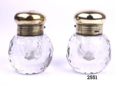 Pair of vintage cut glass inkwells with faceted sides and brass tops (Some signs of wear to the brass tops) Each measures 35mm in diameter at base Main photo of both inkwells side by side