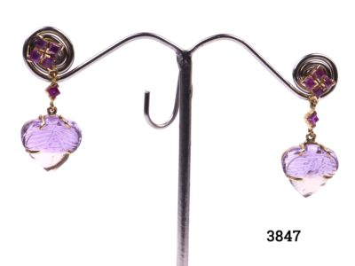 Ametrine and ruby earrings set in 18 carat gold (Ametrine is a variety of quartz with a mixture of amethyst and citrine). Drop length 35mm, 15mm at widest point and approximately 5mm in depth. Main photo showing earrings on a display stand.