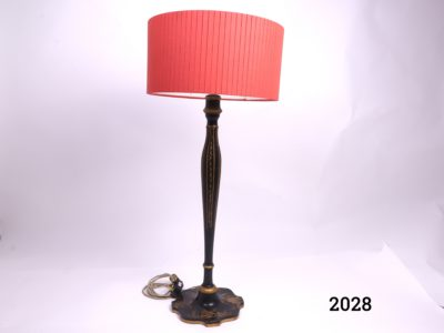 Black lacquered Chinoiserie lamp with Oriental scenes painted in gold to the base and red shade Measures 220mm in diameter at base Shade measures 360mm in diameter Main photo of the whole lamp and shade from side angle