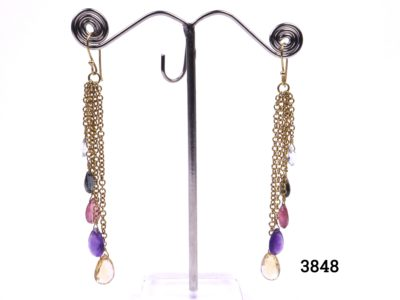 Multi-stone gold dangle earrings set in 18 carat gold with citrine, amethyst, aquamarine, tourmaline and smoky quartz drops on varying lengths of 18 carat gold chain Drop length 85mm and approximately 8mm wide when hanging Main photo of both earrings on display stand