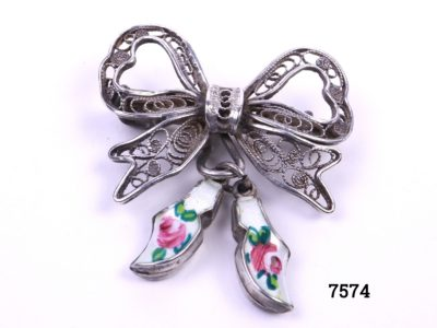 Sterling silver filigree bow brooch with attached pair of silver & enamel white clogs with hand-painted roses to each Main photo showing from of brooch with clogs hanging to the side showing enamelled roses