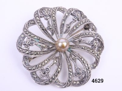 Sterling silver marcasite brooch in a circular floral shape with light bronze coloured faux pearl to the centre Hallmarked silver at the back Measures 40mm in diameter and weighs 11.6g Main photo of front of brooch
