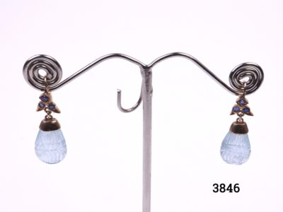 Aquamarine and sapphire earrings set in 18 carat gold. Drop length 35mm and approximately 10mm wide and 5mm deep. Main photo showing both earrings hanging on a display stand.