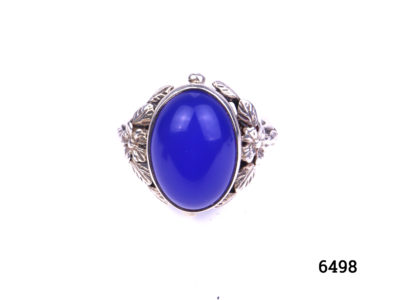 Arts & Crafts ring by Bernard Instone. Hallmarked silver ring set with bright sea blue oval chalcedony stone to centre and floral motifs to the shoulder either side. Size N / 6.5. Main photo showing ring on display stand front view.