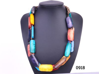 Colourful tagua nut necklace String bound multi-colour stained tagua nut bead statement necklace (Tagua is also known as vegetable ivory) Approximate bead size 40mm x 15mm Main photo showing the multi-coloured necklace displayed on a stand