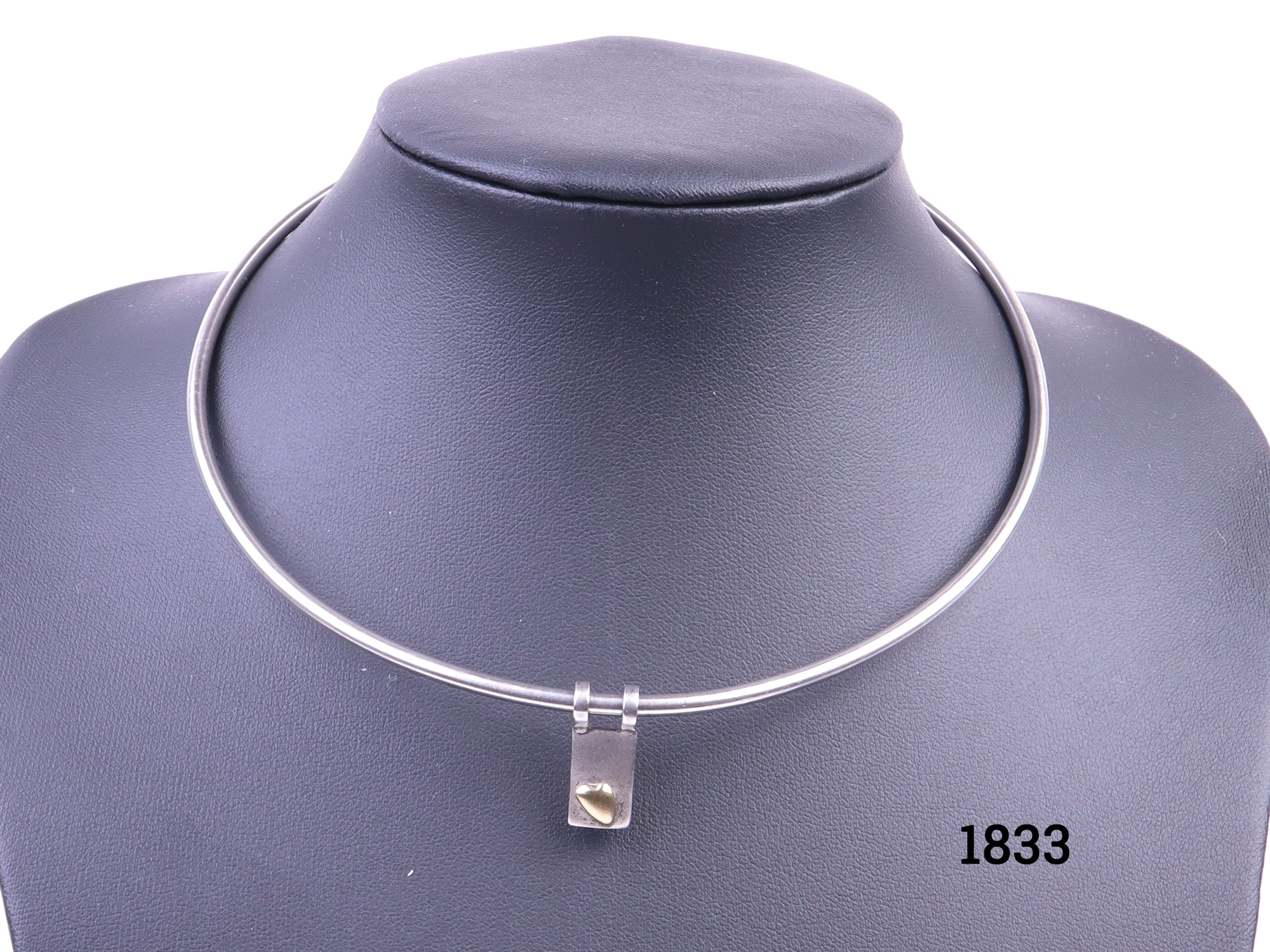 Diana Porter silver necklace in choker style. Hallmarked sterling silver choker style necklace and sterling silver pendant with 18carat gold heart. Necklace width opening 130mm and depth 120mm Pendant size 20mm by 6mm Main photo of necklace on a display stand showing the pendant with gold heart to the front. Other photos shows necklace from the side, on a flat surface and close-up of hallmark on the pendant