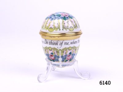 "Egg shaped Halcyon Days pot decorated with hand-painted red roses and forget-me-nots. Inscribed ""Do think of me, when this you see, tho many miles we distant be."" Measures approximately 42mm in diameter Main photo of egg shaped pot displayed on stand"