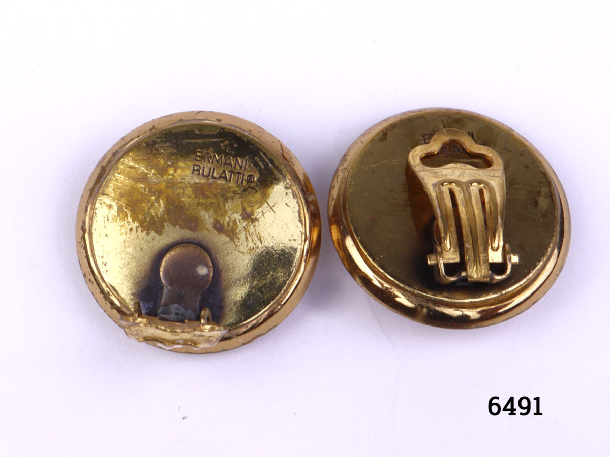 Ermani Bulatti clip-on earrings. Vintage gilt metal circular clip-on earrings with a raised round mound to centre surrounded by inlaid mother-of-pearl (Some gilt wear to centre at front and back). Measures 25mm in diameter Photo of back of both earrings with one clip in open position showing makes mark and gilt wear