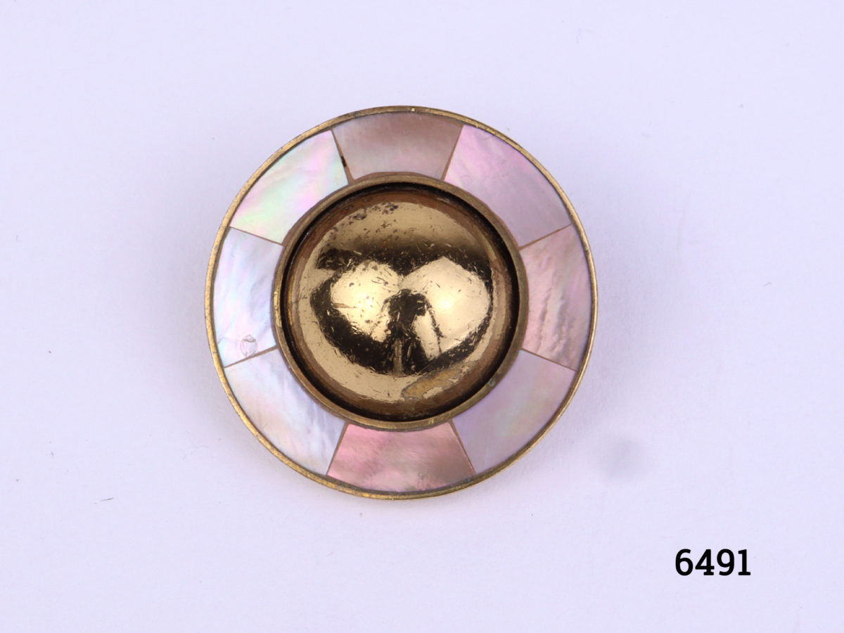 Ermani Bulatti clip-on earrings. Vintage gilt metal circular clip-on earrings with a raised round mound to centre surrounded by inlaid mother-of-pearl (Some gilt wear to centre at front and back). Measures 25mm in diameter Close up photo of front view of one earring