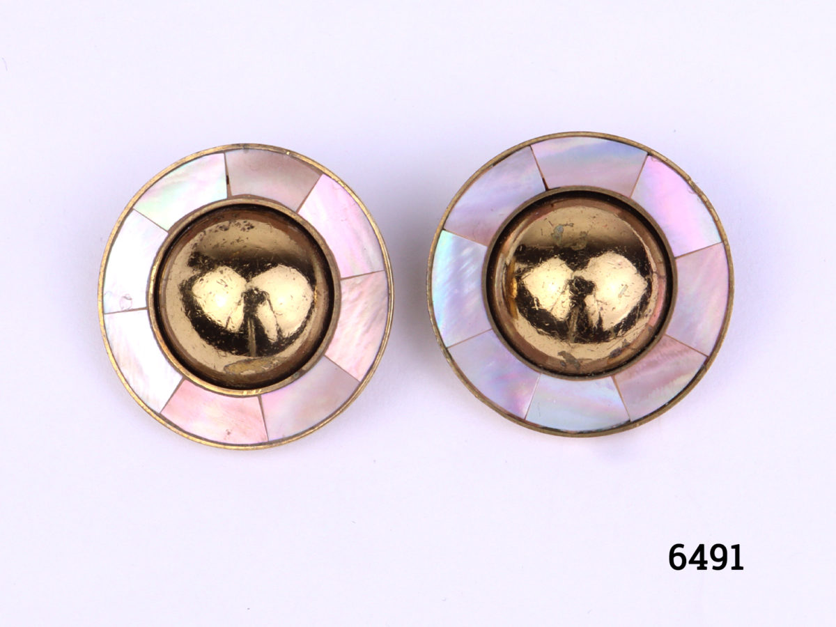 Ermani Bulatti clip-on earrings. Vintage gilt metal circular clip-on earrings with a raised round mound to centre surrounded by inlaid mother-of-pearl (Some gilt wear to centre at front and back). Measures 25mm in diameter Main photo showing front view of both earrings