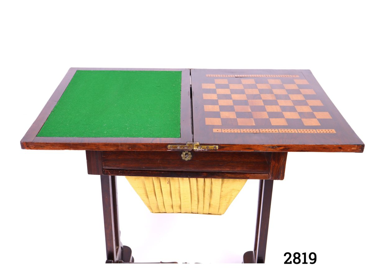 Antique gaming table. Swivel top opens to reveal green felted card playing surface to one side and chess, draughts and cribbage surface on other. Drawer for games pieces below table as well as basket drawer for larger gaming pieces (No games pieces included) Measurements when open Length 765mm Width 510mm Photo of open table top with green felt surface of left and chess board on right