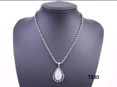 Rainbow (or blue) moonstone teardrop pendant set on 925 sterling silver with ball chain matching the frame around the pendant from Antiques of Kingston
