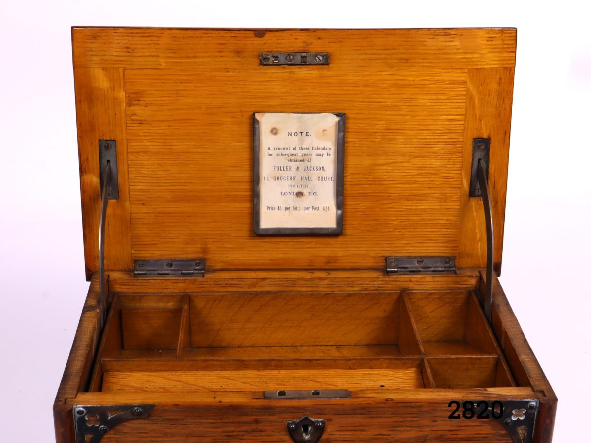 Antique stationery cabinet in wood with brass fittings. Lift lid mechanism to open - front handle decorative only (No key, some signs of wear and handles to the side missing) Measures 282mm wide when open Close up photo of the calendar slot on the inside of lid
