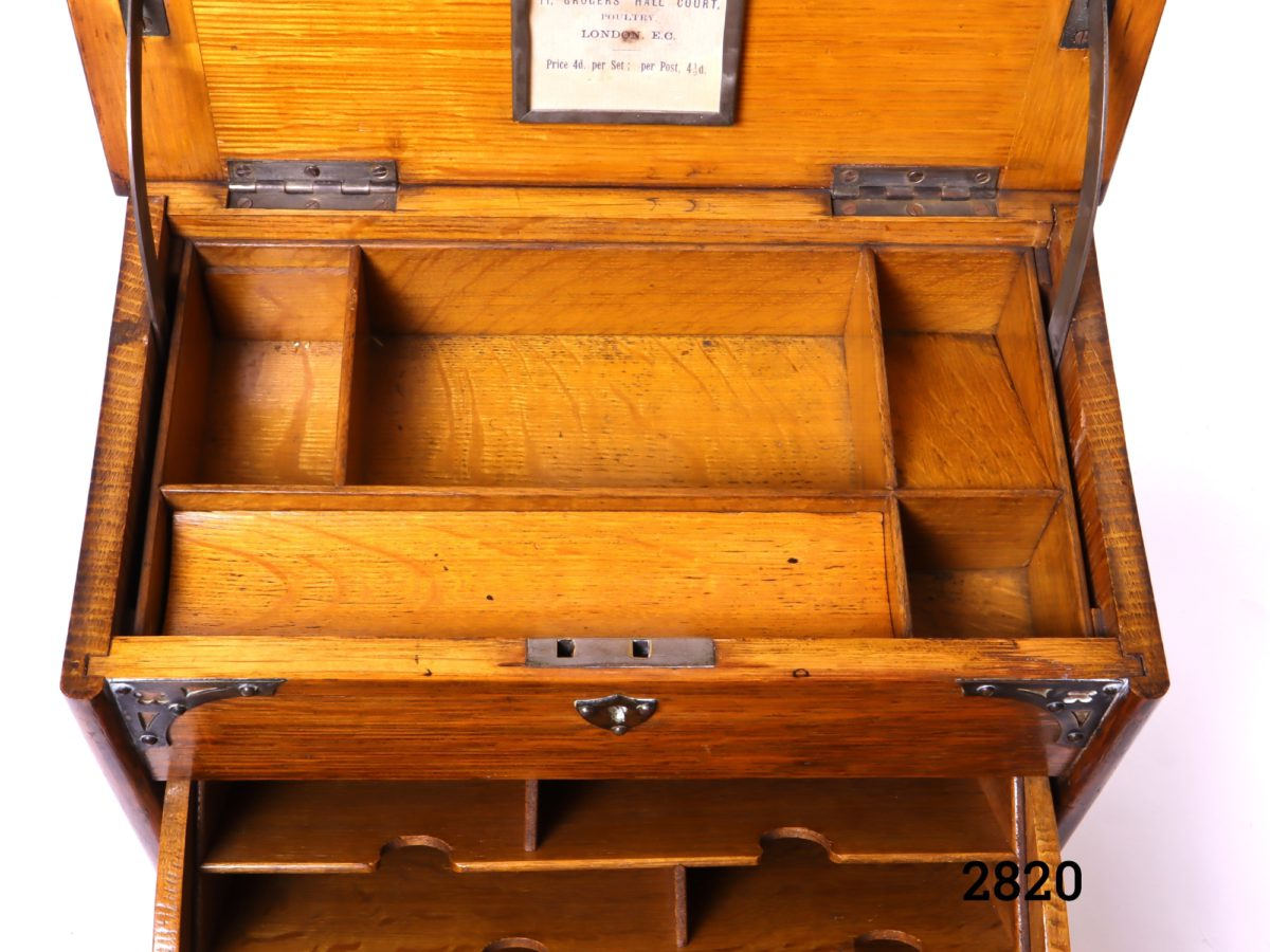 Antique stationery cabinet in wood with brass fittings. Lift lid mechanism to open - front handle decorative only (No key, some signs of wear and handles to the side missing) Measures 282mm wide when open Close up photo showing the interior of the upper section from a front angle