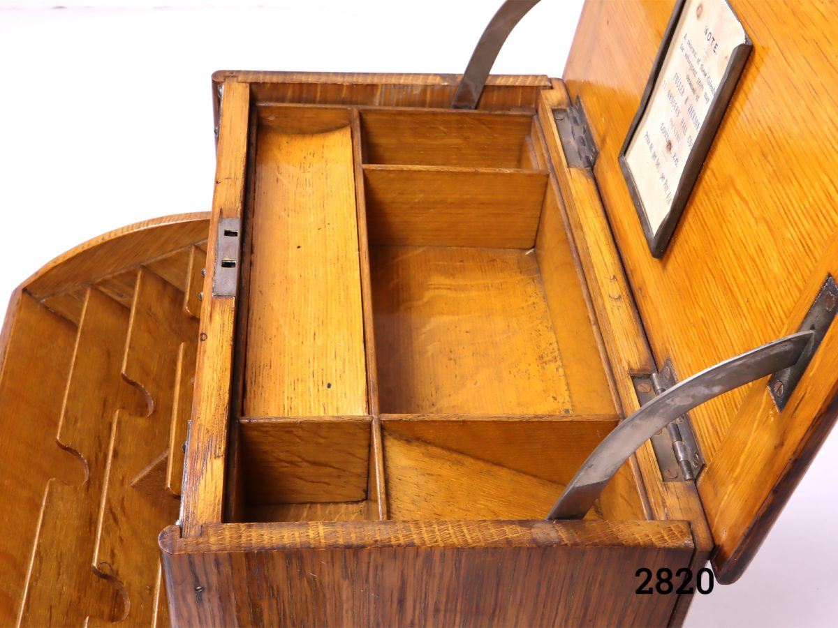 Antique stationery cabinet in wood with brass fittings. Lift lid mechanism to open - front handle decorative only (No key, some signs of wear and handles to the side missing) Measures 282mm wide when open Photo close up of the interior of the upper section from full side angle
