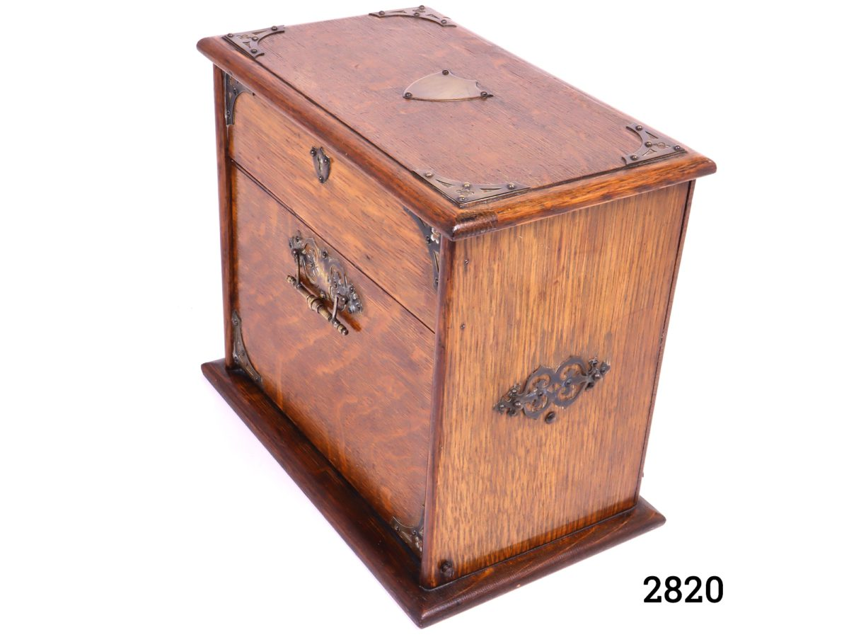 Antique stationery cabinet in wood with brass fittings. Lift lid mechanism to open - front handle decorative only (No key, some signs of wear and handles to the side missing) Measures 282mm wide when open Photo of closed cabinet from a slightly raised side angle