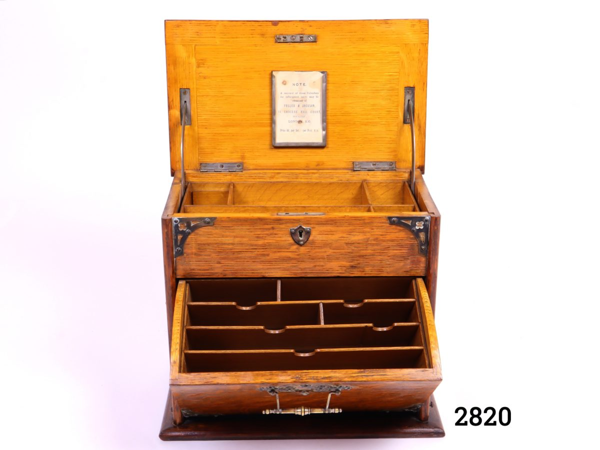 Antique stationery cabinet in wood with brass fittings. Lift lid mechanism to open - front handle decorative only (No key, some signs of wear and handles to the side missing) Measures 282mm wide when open Photo of box from the front fully open showing the letter storage section to the front