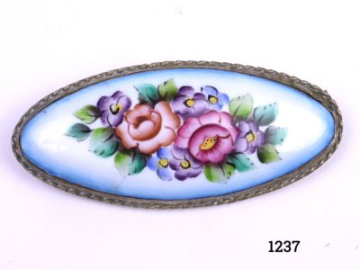 Vintage hand-painted brooch on brass coloured mount with hand-painted multi-coloured enamel flowers Photo showing the front of the brooch displaying the pale blue background with multiple coloured flowers to the centre