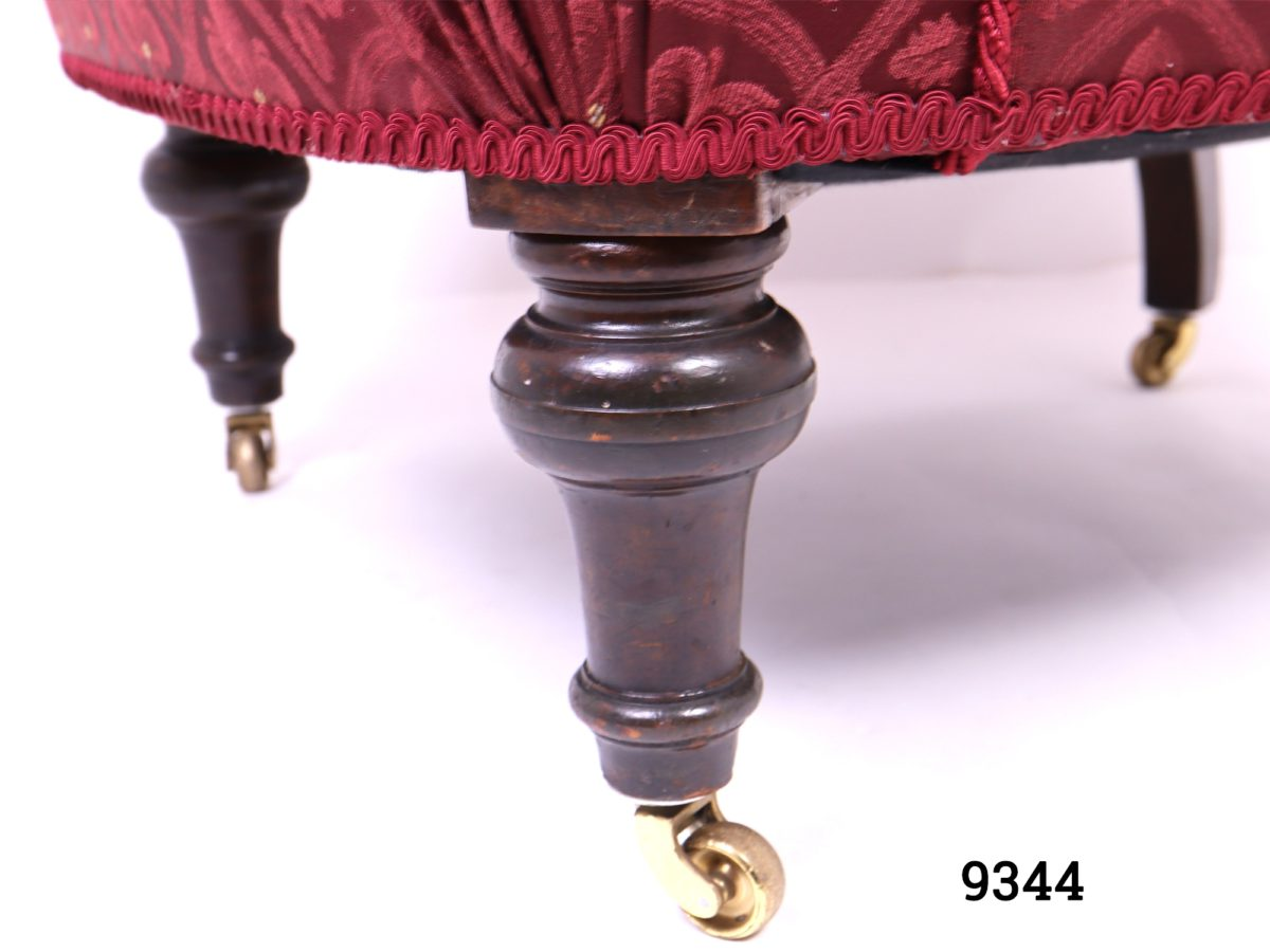 Vintage low armchair in burgundy fleur-de-lis style patterned fabric with button back back rest and wooden legs with brass castors Measures 780mm arm to arm width, 700mm back width and 560mm cushion depth Close up photo of one of the casters