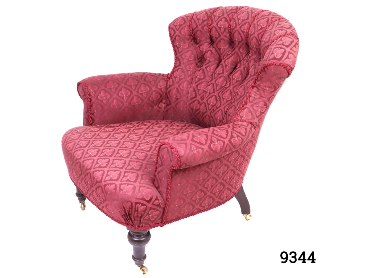 Vintage low armchair in burgundy fleur-de-lis style patterned fabric with button back back rest and wooden legs with brass castors Measures 780mm arm to arm width, 700mm back width and 560mm cushion depth Photo of the chair from a slightly raised side angle