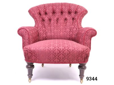 Vintage low armchair in burgundy fleur-de-lis style patterned fabric with button back back rest and wooden legs with brass castors Measures 780mm arm to arm width, 700mm back width and 560mm cushion depth Main photo showing chair from the front