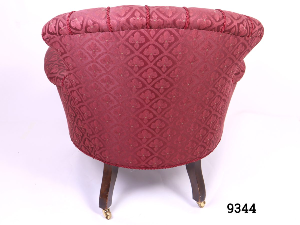 Vintage low armchair in burgundy fleur-de-lis style patterned fabric with button back back rest and wooden legs with brass castors Measures 780mm arm to arm width, 700mm back width and 560mm cushion depth Photo showing the back of chair