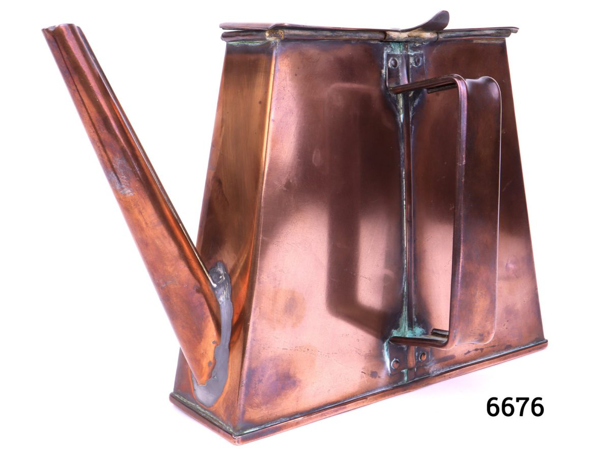 Antique copper watering can in an ingenious space saving shape with handle to the side Barge ware Photo of handle side of watering can