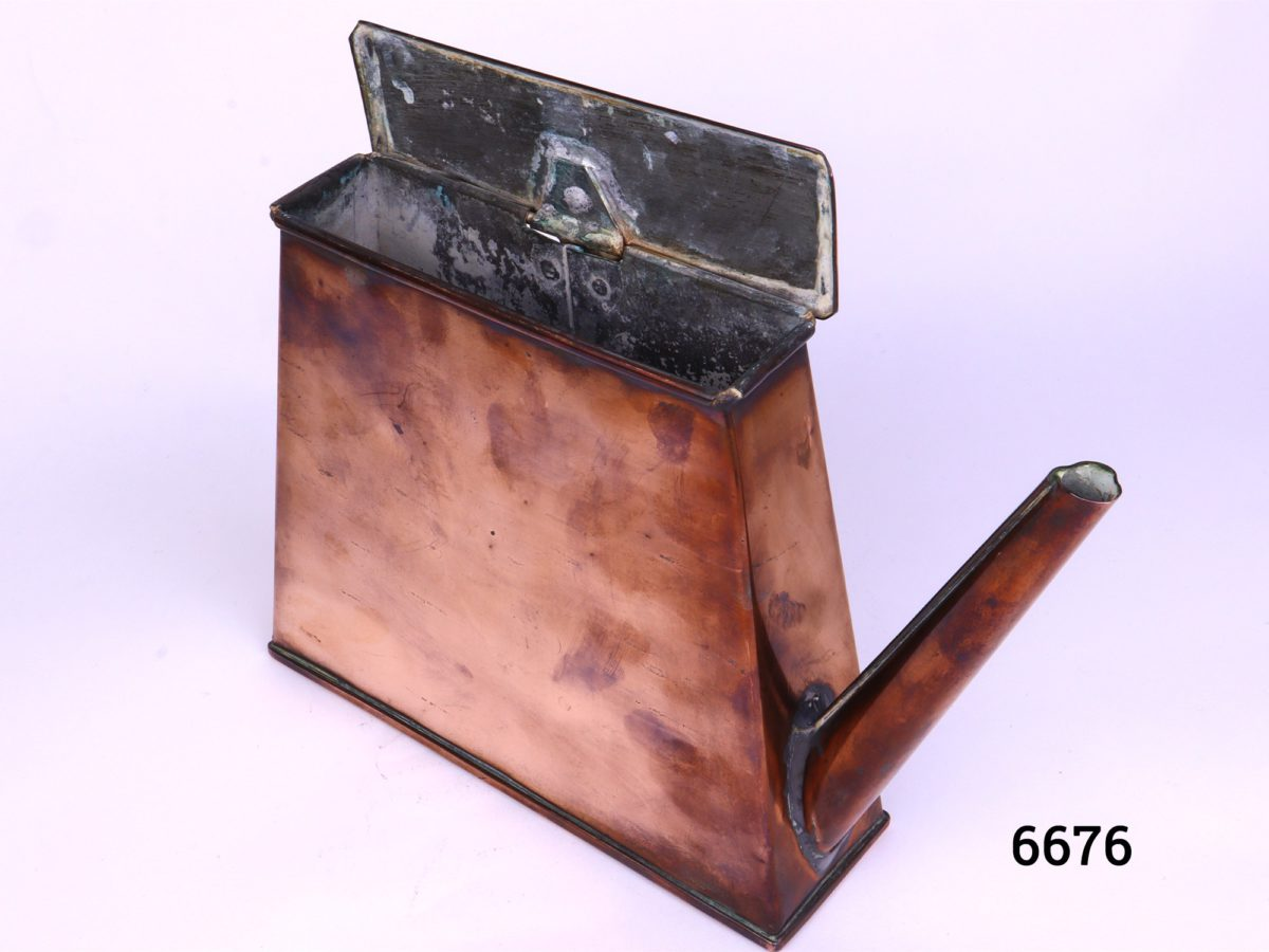 Antique copper watering can in an ingenious space saving shape with handle to the side Barge ware Photo from a slightly raised angle and with top open