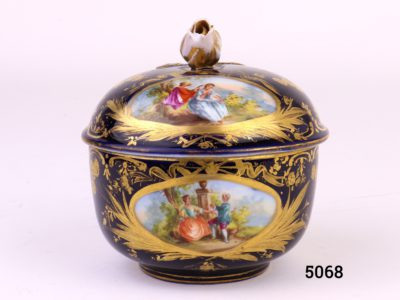 Antique Meissen small lidded bowl in royal blue with gilt throughout and decorated with intricate hand-painted images of courting couples. Rose bud to top of lid intact with minor chips at the edges and some gilt wear. Measures 45mm ín diameter at base and 80mm across the top.                               Base of lid measures 86mm Main photo of pot with lid in place showing 2 of the courting couple scenes
