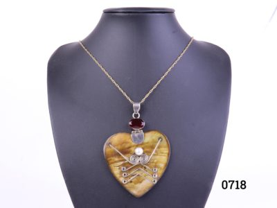 Vintage silver mounted shell heart pendant on a long gilt metal chain. Pendant decorated with faux pearl and red glass stone. Hallmarked 925 on pendant bail. Pendant measures 60mm by 86mm (from bail to bottom of pendant) Main photo showing necklace on a display stand