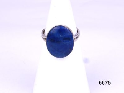 Vintage silver ring with generous size oval lapis lazuli stone from Antiques of Kingston. Hallmarked 980 (Generally Taxco Mexican grade silver). Size P / 7.75. Main photo showing front view of ring which is displayed on a stand.
