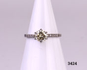 Vintage 1 carat round cut diamond set on new 14karat white gold ring with 12 small vintage diamonds set in the shoulders (6 to each shoulder). SI1 clarity diamond with E to F colour. Gemological Institute of Europe (G.I.E) certified. Box included. Size L.5 / 6 Weight 1.8 grammes Main photo of ring displayed on stand from full front view