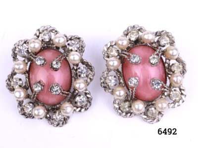 Vintage clip-on earrings with pink glass stone centre decorated with faux pearls and glass stones set on silver coloured metal Measures 35mm by 30mm Both clips in good order Main photo showing fron of earrings
