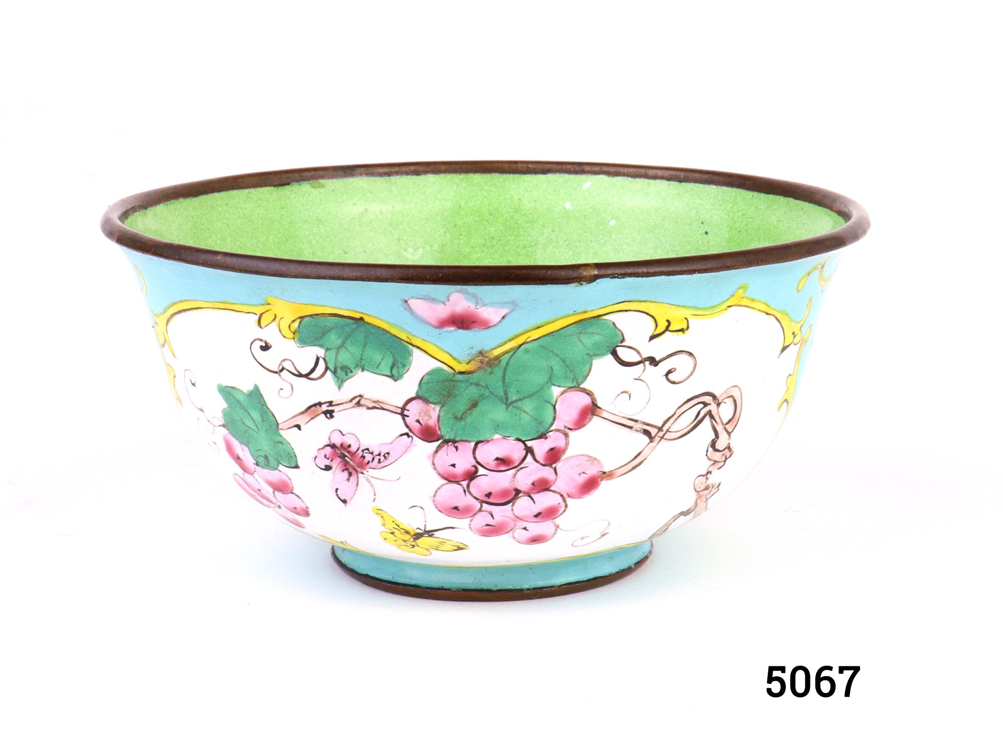 Vintage enamel cloisonne bowl with pale blue exterior decorated with pink grapes with butterflies and lotus flowers with kingfisher. Light green bowl inner decorated with ripening figs Measures 42mm in diameter at base and 100mm across the top Main photo of side view of bowl from the grapes and butterflies decoration side